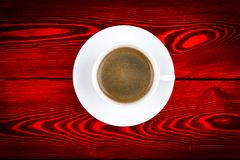 Overhead view of a freshly brewed mug of espresso coffee on red rustic wooden background with woodgrain texture. Coffee break Stock Images