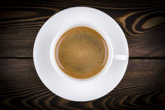Overhead view of a freshly brewed mug of espresso coffee on rustic wooden background with woodgrain texture. Coffee break style. Royalty Free Stock Photos
