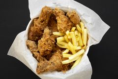 Overhead view, fried chicken drumsticks, spicy wings, French fries and chicken strips in paper box on black background. Flat lay,. Top view, from above stock photography
