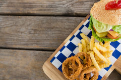Overhead view of fried onion rings with french fries by burger Royalty Free Stock Photo
