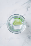Overhead view gin and tonic with lime and cucumber on a marble background Royalty Free Stock Images