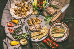 Overhead view of grilled pork steak with roast and fresh vegetables, plates and knife on rustic wooden. Table. Rustic food stock photos