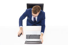 Overhead view of a handsome businessman working in office on a laptop. Business and office concept Stock Photos