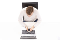 Overhead view of a handsome guy working in office on a laptop. Business and office concept.  Royalty Free Stock Image