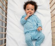 Overhead view of a happy baby boy lying in a crib. Wearing pajamas stock photography