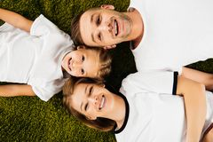 Overhead view of happy family in similar clothing lying. On green lawn stock image