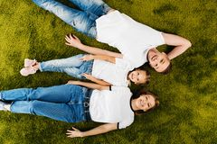 Overhead view of happy family in similar clothing lying. On green lawn stock photos