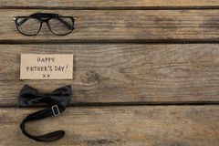 Overhead view of happy fathers day text with eyeglasses and bow tie Stock Image