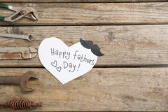 Overhead view of happy fathers day text by work tools. On wooden table stock image