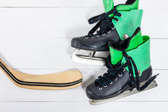 Overhead view of hockey stick and ice skates on white wooden tab Stock Photo