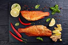 Overhead view of hot smoked red snappers. On a black stone plate with spices, herbs and sliced lemons, view from above, flatlay stock image