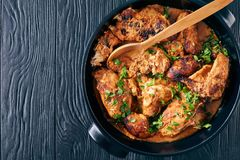 Overhead view of Kuku Paka, Kenyan chargrilled Chicken in creamy spicy Coconut gravy in a earthenware saucepan on a black wooden royalty free stock image