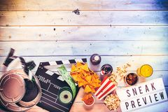 Overhead view of large film reel and tickets. Overhead view of brightly lit metal large film reel and rolled up tickets and food and drinks and lettered sign Stock Images