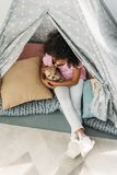 Overhead view of little cute african american kid with chihuahua dog in teepee. At home royalty free stock images
