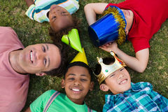 Overhead view of man with children lying on field stock image