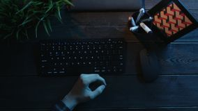 Overhead view of man drinking coffee while sitting in front of computer. Top down shot of man drinking coffee while sitting in front of computer by wooden office stock video footage