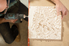 Overhead View of Man Perforating a Plaster Model with Drill Royalty Free Stock Image