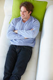 Overhead View Of Man Relaxing On Sofa. With His Arms Crossed Smiling stock image