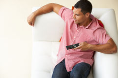 Overhead View Of Man Relaxing On Sofa Watching Television Stock Photography
