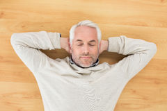 Overhead view of a man sleeping on parquet floor. Overhead view of a mature man sleeping on parquet floor at home Stock Image