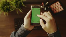 Overhead view of man using his smartphone with green screen stock footage