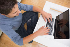 Overhead view of a man using laptop in living room Stock Images