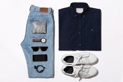 Overhead view of men`s casual outfits, Outfits of traveler, male. Shirt,jean,wallet,watch,sunglasses,phone,earphone shoe.Overhead view of men`s casual outfits Stock Photography