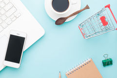 Overhead view of modern work space with laptop, mobile device and shopping cart Royalty Free Stock Images
