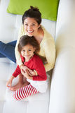 Overhead View Of Mother And Daughter Relaxing On Sofa royalty free stock photo
