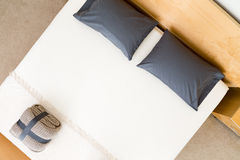 Overhead view of a neat king size bed. In a hotel or house with black pillows on a white counterpane with a folded and strapped rug at the food and a wooden Stock Photos