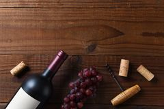Overhead View Of A Cabernet Sauvignon Wine Bottle On A Dark Wood Surface With Grapes And Cork Screw Corks And Copy Space Stock Photo
