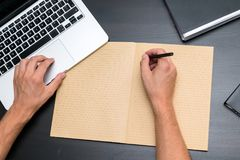 Overhead view of office table with mans hands writing with pen o royalty free stock images