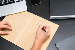 Overhead view of office table with mans hands writing to do list stock image