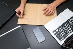 Overhead view of office table with mans hands writing to do list royalty free stock photo