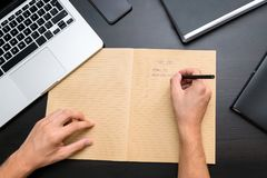 Overhead view of office table with mans hands writing to do list stock images