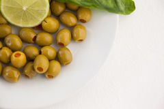 Overhead view of olives with lemon in plate stock photography