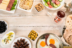 Overhead view of oriental breakfast. With naan, turkish Suck meat sunny side up eggs, dates, hummus and tasty arabic tea. On rustic white wooden background with stock image