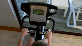 Overhead view of person using exercise bike in gym. An overhead, above view of a young woman using an exercise bike in a gym stock video