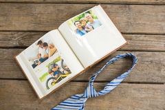 Overhead view of photo album by necktie on table Royalty Free Stock Image