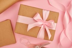 Pink satin ribbon and scissors near present box on pink flatlay Royalty Free Stock Images