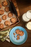 Warm plate of chocolate chip cookies and milk. Overhead view of plate and cookie sheet of chocolate chip cookies warm from the oven with glass of milk on vintage Royalty Free Stock Image
