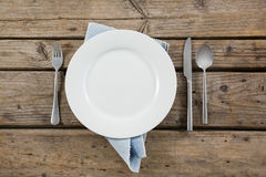 Overhead view of plate and cutlery with napkin. On wooden table Royalty Free Stock Image