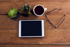 Pot plant, black coffee, spectacles and digital tablet on wooden table. Overhead view of pot plant, black coffee, spectacles and digital tablet on wooden table Royalty Free Stock Images