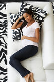 Overhead View Of Pregnant Woman Relaxing On Sofa Stock Photo