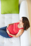 Overhead View Of Pregnant Woman Relaxing On Sofa Stock Images