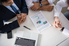 Overhead view of professional businessmen discussing charts at workplace Royalty Free Stock Photos