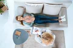 Overhead view of psychologist writing on clipboard and young woman. Overhead view of psychologist writing on clipboard and young women lying on couch stock photo