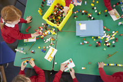Overhead View Of Pupils Working With Coloured Blocks Stock Photo