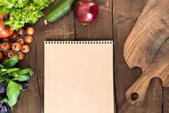 Overhead view of raw vegetables, chopping board and blank notepad on wooden table. Food composition background Stock Photo