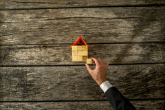 Overhead view of real estate or insurance agent constucting a ho. Overhead view of real estate or insurance agent constructing a house from a wooden cubes Royalty Free Stock Images